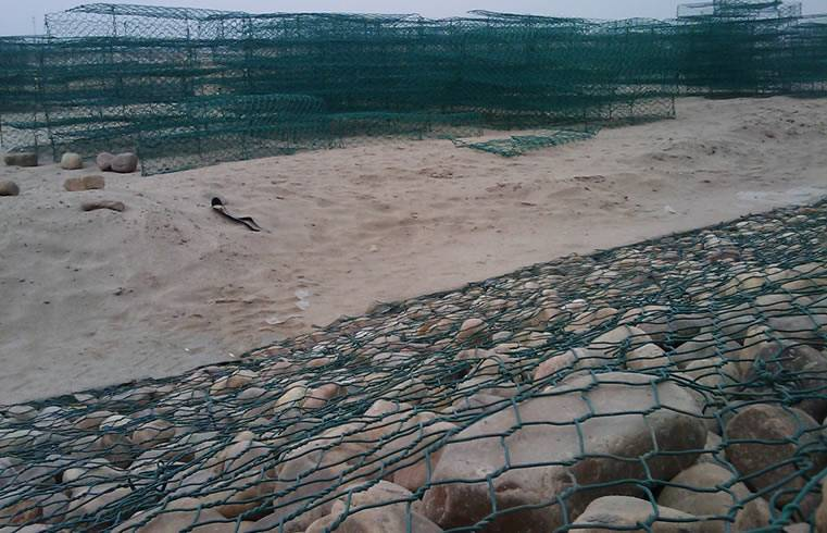 A hexagonal woven double twisted dark green PVC coated gabion box on the ground.