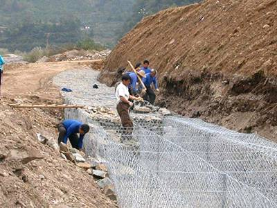 Several workers are filling the gabion box with stones.