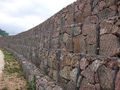 Four layers of gabion boxes on the ground.