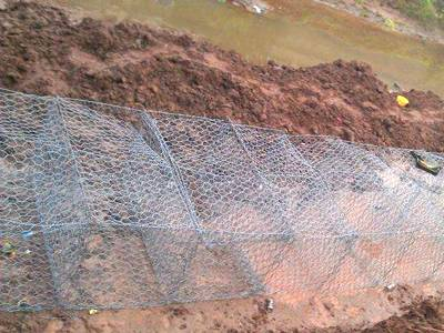 Several gabion boxes are raised and up on the ground.
