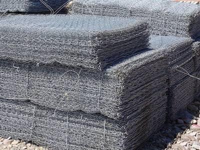Several bundles of gabion mattress on the ground.