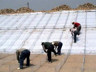 Five workers are fastening the gabion mattress using lacing wire.