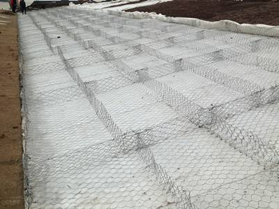 Several cells of gabion mattress are placed on the slope.