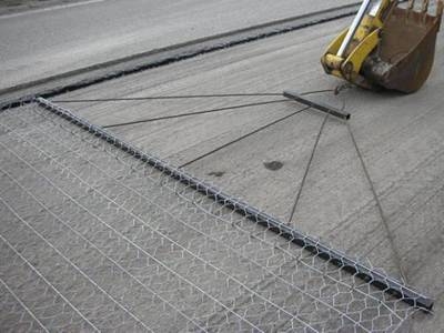 A machine is stretching the road mesh on the road.