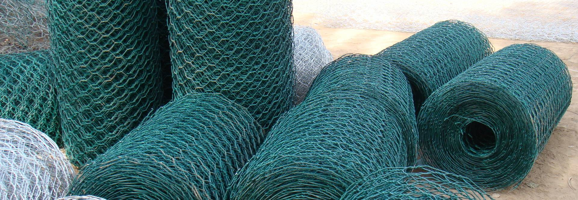 Many rolls of blue PVC coated poultry mesh.