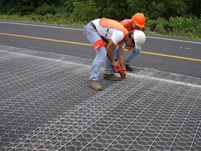 Two workers are laying the road mesh on the city road.