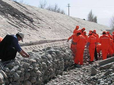 Several workers are placing the sack gabion at the foot of dam.