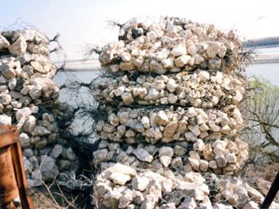 Several sack gabions are piled up beside of the river.