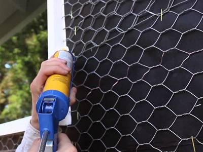 A worker is install the stucco netting onto the wall.