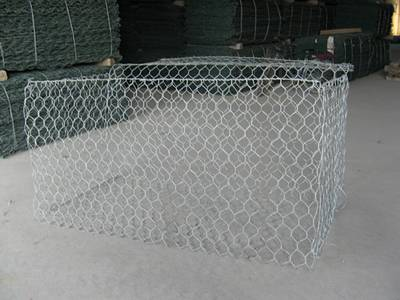 A galvanized woven gabion box on the ground.