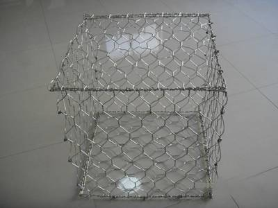 A galvanized woven gabion on the ground.