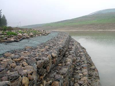 Galvanized woven gabions are installed on the bank of river.